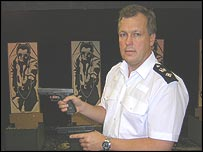 Ch Supt Paul Robinson holding real and fake pistols