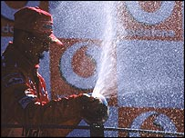 Michael Schumacher sprays champagne on the podium after winning the 2004 Italian Grand Prix