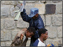 An Ethiopian policeman beating a university student using the butt of his assault rifle