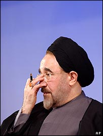 Iranian President Khatami adjusts his glasses as students shout slogans during his speech
