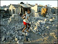 A child jumps through the ruins of destroyed homes in Harare