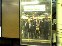 Japanese commuters reflected in platform mirrors
