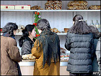 North Korean women gather at a stall to buy food items in Pyongyang, 14 February 2003.