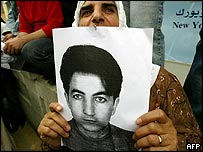 A Syrian holds a picture of Rashid Mahmood al-Sheikh, demanding his release from jail