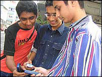 Indian boys using a mobile phone, BBC