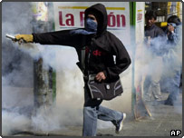 A demonstrators throws a tear gas canister back at riot police officers during clashes in La Paz, Bolivia