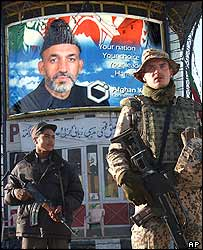 An Afghan security guard and a German peacekeeper in front of a poster of Hamid Karzai
