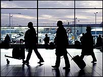 Travellers walking through an airport