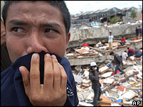 Man covers his nose with his cloth at a damaged site on Nias island following the earthquake on 28 March 2005