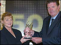 Glenda Charles collects the award on behalf of her late husband from Wales football manager John Toshack