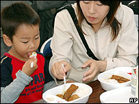 Japanese family eating food made from whale meat, May 2005