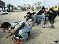 Palestinian youths take cover from Israeli fire in Gaza City