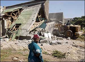 Woman watches her house being destroyed