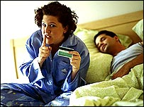 Woman in bed with credit card