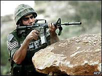 Israeli border guard shoots rubber bullets during clashes with Palestinians in the West Bank village of Budrus, 7 December 2004