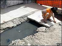 A little girl plays by sewage in Sadr City, Baghdad