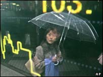 A Japanese woman shelters from the rain in front of a yen graph in a shop window
