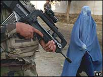 A woman wearing a burka walks past a soldier in Kabul