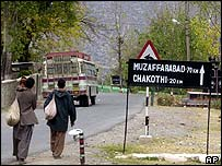 Kashmiris near a sign showing the distance to Muzaffarabad
