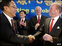 Lenovo chairman Liu Chuanzhi shakes hands with John Joyce, IBM senior vice president