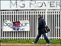 Worker walking past MG Rover plant and protest banner