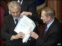 Ukraine's parliamentary speaker Volodymyr Lytvyn (left) and outgoing President Leonid Kuchma hold the signed text of the amendments