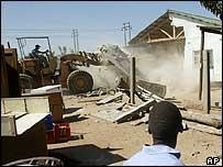 Boy watching house being demolished