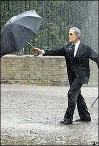 A Greenpeace activist dressed as President Bush dances under the artificial rain