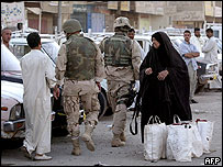 US soldiers walk past Iraqi woman while on patrol in Baghdad