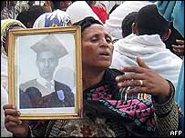 A mother holds the photo of her dead son at his funeral