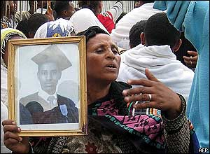 A mother holds the photo of her son at his funeral