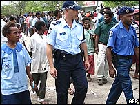 An Assisting Australian Police (AAP) officer (C) joins his Papua New Guinean counterpart (R)