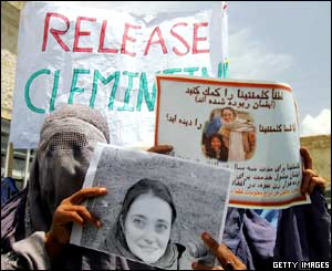 Afghan war widows display portraits of Clementina Cantoni during a demonstration at a Care International food distribution centre in Kabul.