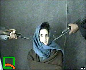Clementina Cantoni sits between two men holding assault rifles pointed at her head in this frame taken from a video broadcast by an Afghanistan television station.