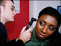 Photo of woman having her ear examined