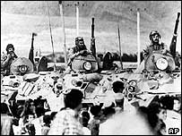 Soviet armour moves past Afghan civilians during withdrawal in 1988