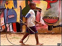 Boy walks past graffiti, Mozambique