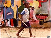 Boy walks past graffiti, Mozambique