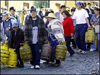 Bolivians carrying gas bottles