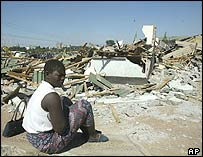 A woman sits by her demolished home in Harare