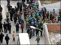 Workers and police in Beijing following a protest over demolitions 15/11/04