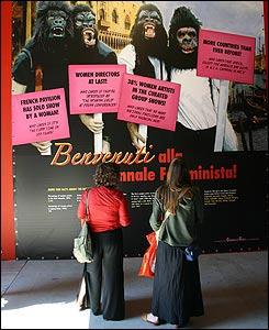 """Dos mujeres frente a una obra que dice """"�Bienvenidos a la Bienal Feminista!"""", de Guerrilla Girls."""