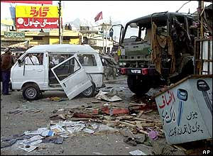 Local residents look at damaged vehicles after an explosion in Quetta, Pakistan