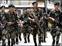 Filipino soldiers prepare to deploy behind the compound housing a Catholic seminary at the financial district of Makati city east of Manila on Monday June 13, 2005