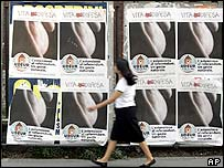 Woman walks past posters advocating abstention