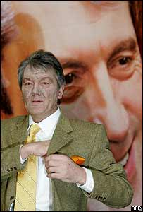 Viktor Yushchenko speaks to reporters under a poster showing his face as it was, 10 December 2004