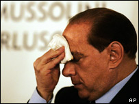 Italian Prime Minister Silvio Berlusconi wipes his brow