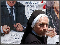 "Nun walking past a poster reading: ""The referendum on assisted fertility will make the future of many couples. I vote yes"""
