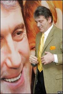 Viktor Yushchenko walks past an earlier image of himself
