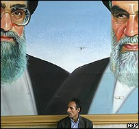 Iranian man sits in front of a mural depicting Islamic leaders